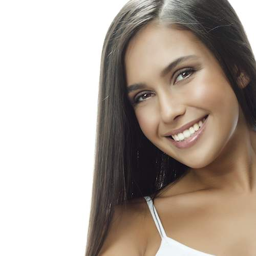 A pretty yong girl with long hair and a bright white smile thanks to teeth whitening in Seattle WA from Downtown Dentistry