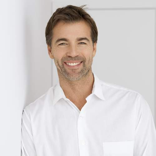 A middle-aged man smiling to show the impact restorative dentistry can have on your smile.