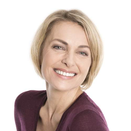 A woman smiles to illustrate how crowns & bridges can restore and even improve your smile