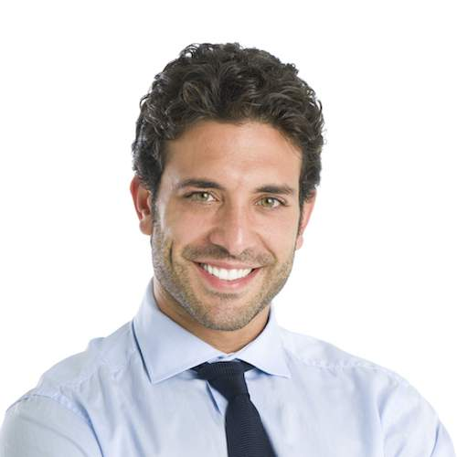 A businessman smiles to show off the benefits of porcelain veneers treatments in achieving your dream smile.