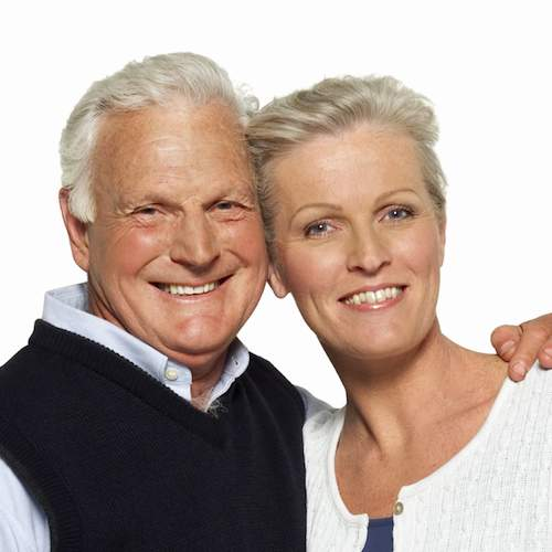 A smiling elderly couple illustrates the benefits of partial dentures for smile restoration.