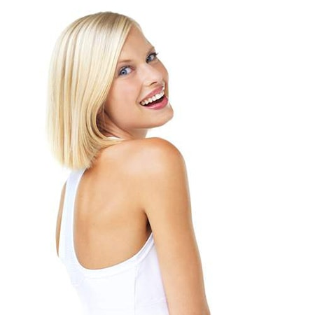 An attractive woman looking over he shoulder at the camera and smiles to show off her cosmetic dentistry work performed by Seattle dentist, DR. Curtis