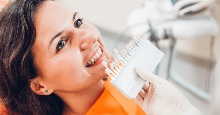 A young woman in a dentist chair choosing the whiteness color of her teeth.