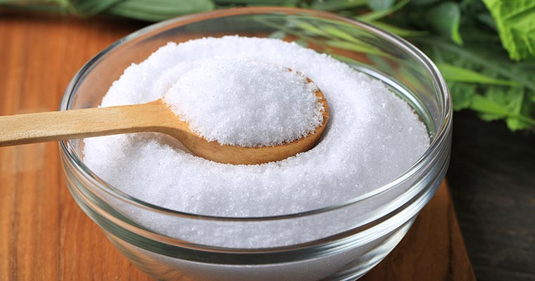 A wooden spoon in a glass bowl full of xylitol for dental health.